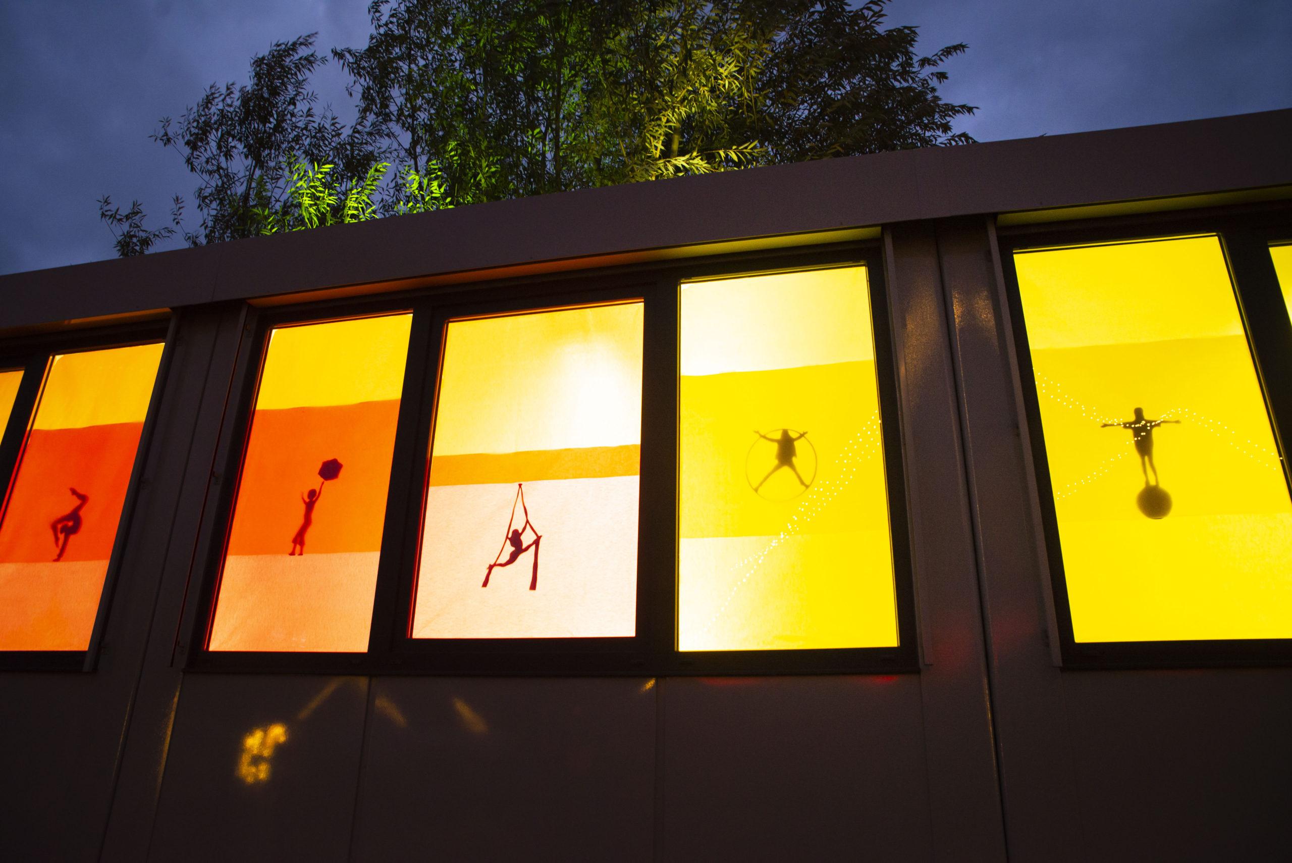 Bunte Fenster lassen den Bürocoantainer einer gigantischen Laterne ähneln